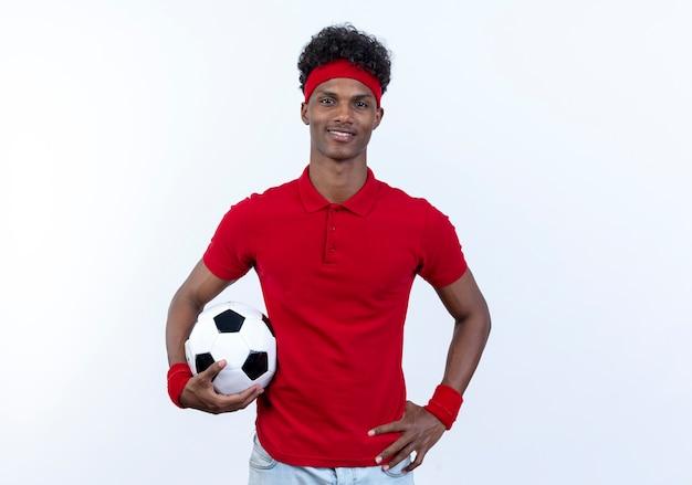 Erfreulicher junger afroamerikanischer sportlicher mann, der stirnband und armband hält ball hält und hand auf hüfte lokalisiert auf weißem hintergrund setzt