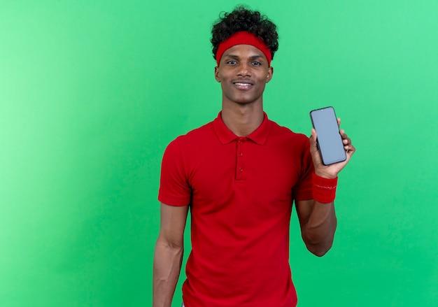 Erfreulicher junger afroamerikanischer sportlicher mann, der stirnband und armband hält telefon lokalisiert auf grüner wand trägt