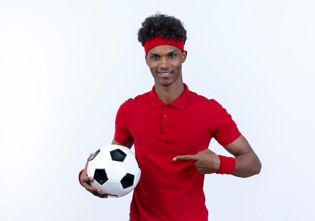 Erfreulicher junger afroamerikanischer sportlicher mann, der stirnband und armband hält und punkte auf kugel lokalisiert auf weißem hintergrund trägt