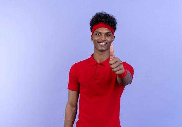 Erfreulicher junger afroamerikanischer sportlicher mann, der stirnband und armband seinen daumen oben isoliert auf blauem hintergrund trägt
