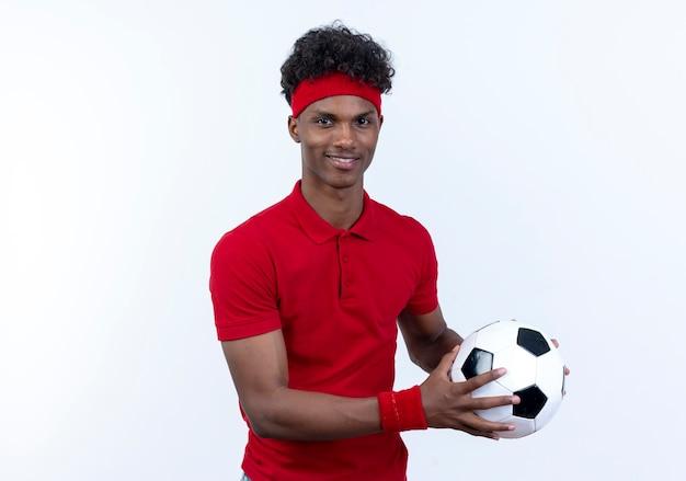 Erfreulicher junger afroamerikanischer sportlicher mann, der stirnband und armband trägt, hält ball zur seite lokalisiert auf weißem hintergrund