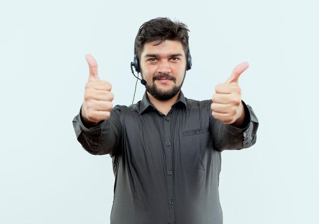 Erfreulicher junger call-center-mann, der headset trägt, seine daumen oben lokalisiert auf weißem hintergrund