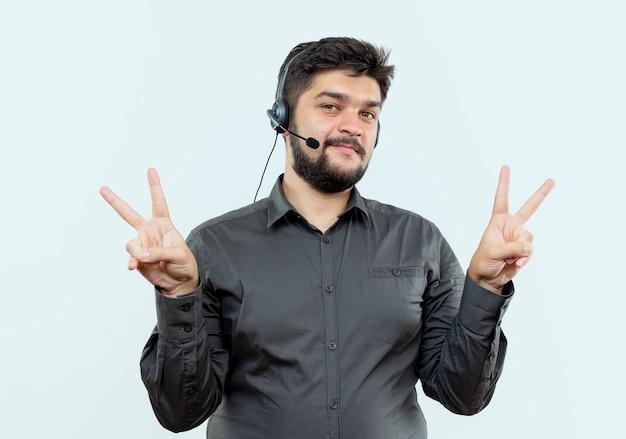 Erfreulicher junger callcenter-mann, der headset trägt, das friedensgesten lokalisiert auf weißem hintergrund zeigt