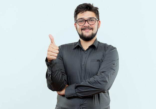 Erfreulicher junger geschäftsmann, der brille seinen daumen oben auf weißem hintergrund trägt