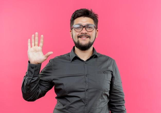 Erfreulicher junger geschäftsmann, der brille trägt, die fünf lokalisierte auf rosa wand zeigt