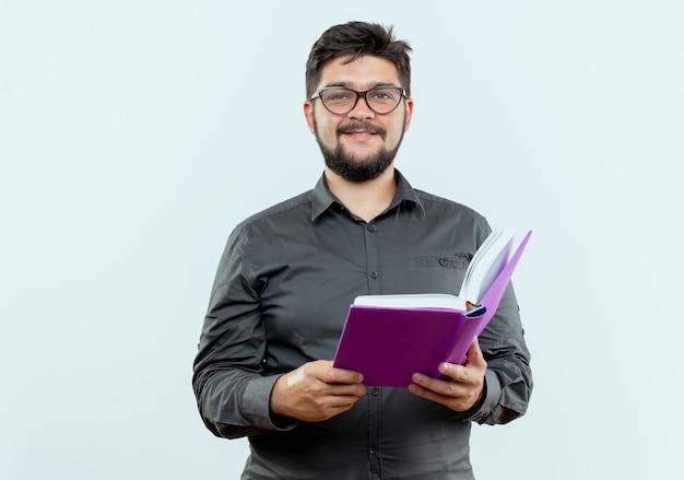 Erfreulicher junger geschäftsmann, der brillen hält buch lokalisiert auf weißem hintergrund trägt