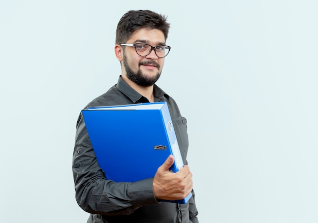 Erfreulicher junger geschäftsmann, der brillen hält ordner isoliert auf weißem hintergrund