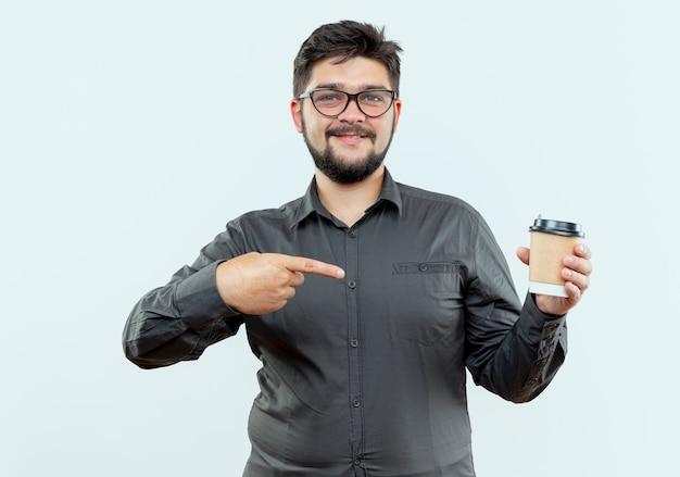 Erfreulicher junger geschäftsmann, der brillen hält und punkte auf tasse kaffee lokalisiert auf weißem hintergrund trägt