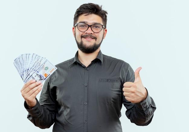 Erfreulicher junger geschäftsmann, der brillen trägt, die bargeld seinen daumen oben lokalisiert auf weißem hintergrund halten