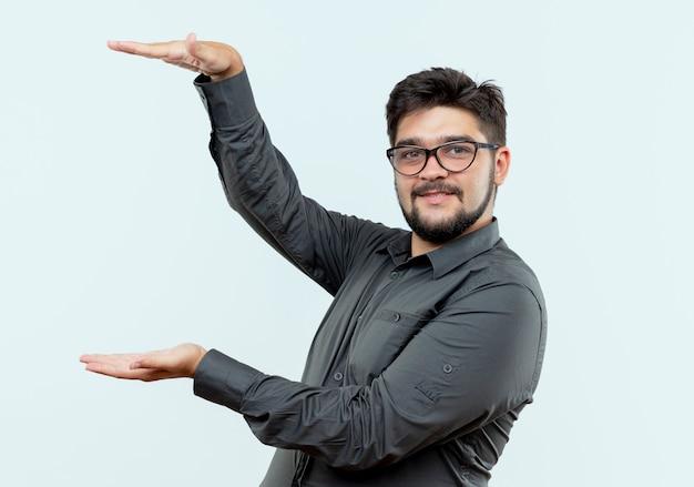 Erfreulicher junger geschäftsmann, der brillen trägt, die größe lokalisiert auf weißem hintergrund zeigen