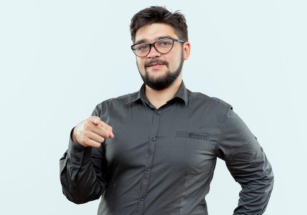 Erfreulicher junger geschäftsmann, der brillen trägt, die sie geste lokalisiert auf weißem hintergrund zeigen