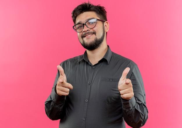 Erfreulicher junger geschäftsmann, der brillen trägt, die sie gesten zeigen, die auf rosa wand lokalisiert werden