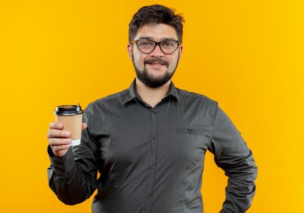 Erfreulicher junger geschäftsmann, der brillen trägt, die tasse kaffee lokalisiert auf gelber wand halten
