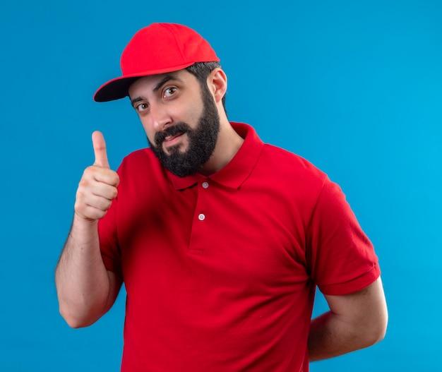 Erfreulicher junger gutaussehender lieferbote, der rote uniform und mütze trägt, die daumen oben zeigt und hand hinter dem rücken lokalisiert auf blauer wand hält