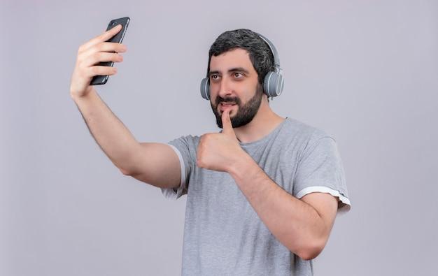 Erfreulicher junger gutaussehender mann, der kopfhörer trägt, daumen zeigt und selfie lokalisiert auf weißer wand nimmt