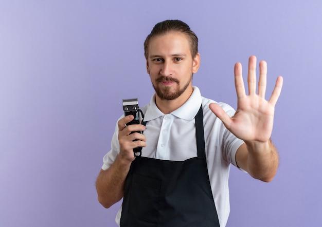 Erfreulicher junger hübscher friseur, der uniform hält, die haarschneidemaschine hält und hand nach vorne streckt, lokalisiert auf lila wand