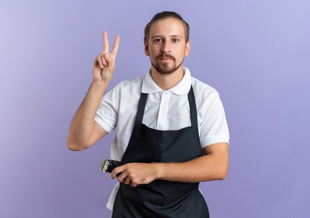 Erfreulicher junger hübscher friseur, der uniform trägt, die friedenszeichen tut und haarschneidemaschinen in einer anderen hand hält, die front lokalisiert auf lila wand betrachtet