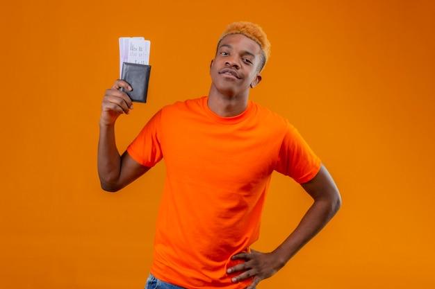 Erfreulicher junger hübscher junge, der orange t-shirt hält, das das flugticket hält, das zuversichtlich steht, über orange wand zu stehen