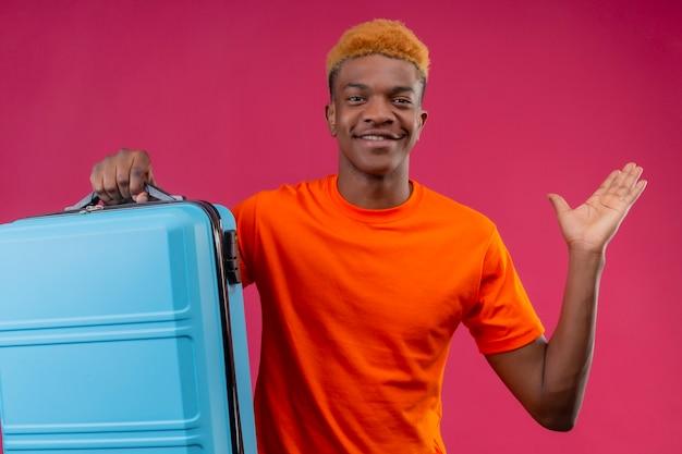 Erfreulicher junger hübscher junge, der orange t-shirt hält, das reisekoffer hält, der glücklich und positiv mit erhöhtem arm steht, der über rosa wand steht
