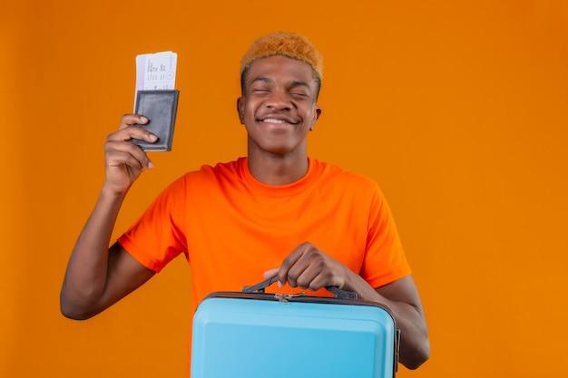 Erfreulicher junger hübscher junge, der orangefarbenes t-shirt hält, das reisekoffer und flugtickets hält, die glücklich lächeln und sich freuen, seinen erfolg zu genießen, der über der orangefarbenen wand steht