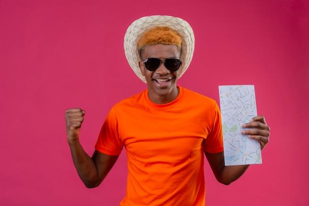 Erfreulicher junger hübscher junge im sommerhut, der orange t-shirt hält karte hält