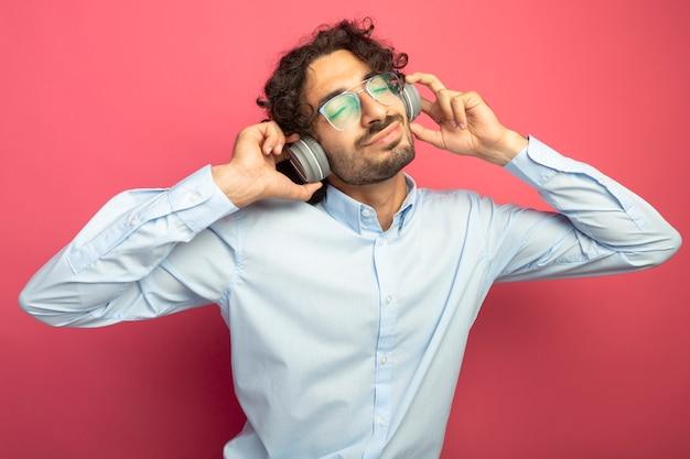 Erfreulicher junger hübscher kaukasischer mann, der brille und kopfhörer trägt, die kopfhörer greifen, die musik mit geschlossenen augen lokalisiert auf purpurrotem hintergrund hören