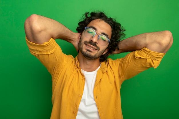 Erfreulicher junger hübscher kaukasischer mann, der brillen trägt, die hände hinter kopf mit geschlossenen augen lokalisiert auf grünem hintergrund setzen