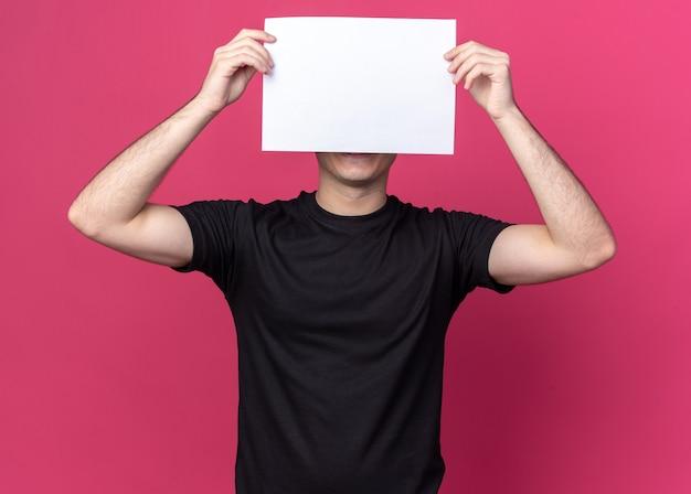Erfreulicher junger hübscher kerl, der schwarzes t-shirt bedecktes gesicht mit papier lokalisiert auf rosa wand trägt