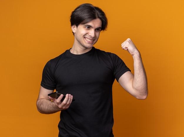 Erfreulicher junger hübscher kerl, der schwarzes t-shirt hält telefon hält und ja geste auf orange wand isoliert zeigt