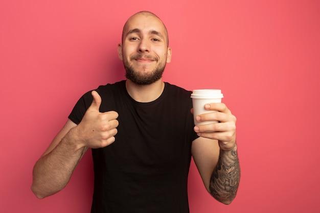 Erfreulicher junger hübscher kerl, der tasse kaffee hält und daumen zeigt