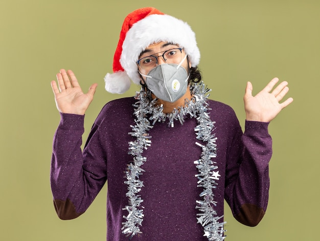 Erfreulicher junger hübscher kerl, der weihnachtshut und medizinische maske mit girlande am hals trägt, die hände lokalisiert auf olivgrünem hintergrund verbreiten