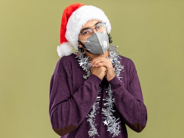Erfreulicher junger hübscher kerl, der weihnachtsmütze und medizinische maske mit girlande am hals hält, die hände zusammen lokalisiert auf olivgrünem hintergrund hält