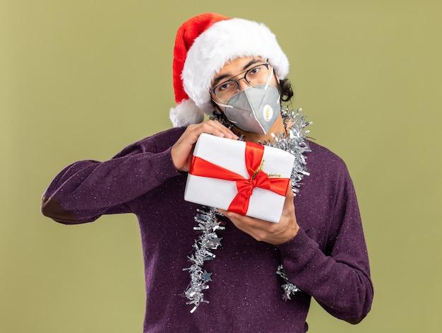 Erfreulicher junger hübscher kerl, der weihnachtsmütze und medizinische maske mit girlande am hals hält geschenkbox lokalisiert auf olivgrünem hintergrund trägt