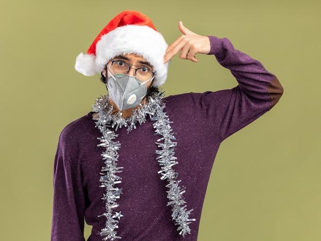 Erfreulicher junger hübscher kerl, der weihnachtsmütze und medizinische maske mit girlande am hals trägt, die selbstmord mit pistolengeste lokalisiert auf olivgrünem hintergrund zeigt