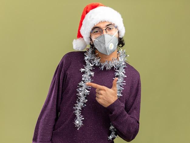 Erfreulicher junger hübscher kerl, der weihnachtsmütze und medizinische maske mit girlande auf halspunkten an der seite trägt, lokalisiert auf olivgrünem hintergrund mit kopienraum
