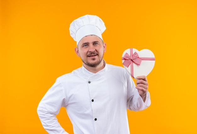Erfreulicher junger hübscher koch in der kochuniform, die herzförmige geschenkbox hält und finger auf isoliertem orange raum hebt
