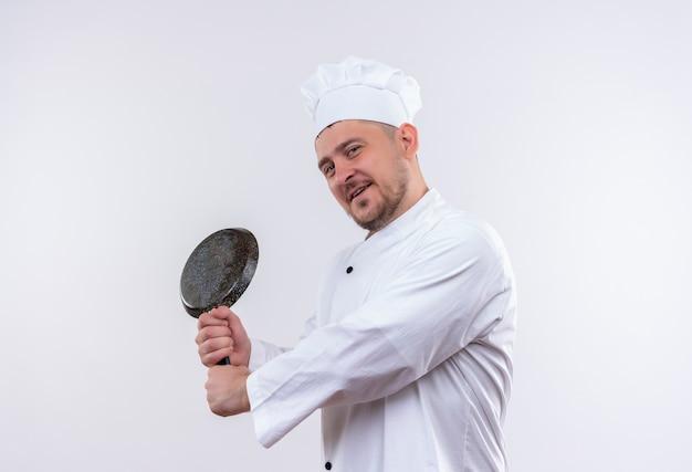 Erfreulicher junger hübscher koch in der kochuniform, die in der profilansicht hält, die bratpfanne lokalisiert auf weißem raum hält
