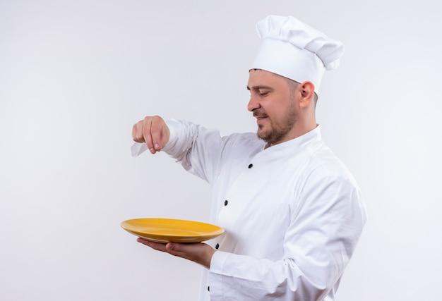 Erfreulicher junger hübscher koch in der kochuniform, die in der profilansicht hält platte hält und salz verschüttet, das auf weißem raum isoliert wird