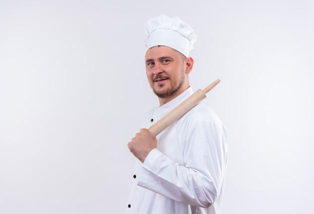 Erfreulicher junger hübscher koch in der kochuniform, die in der profilansicht steht und nudelholz lokalisiert auf weißem raum hält