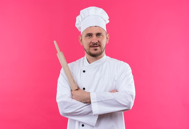 Erfreulicher junger hübscher koch in der kochuniform, die nudelholz hält und mit geschlossener haltung steht, die auf rosa raum lokalisiert wird