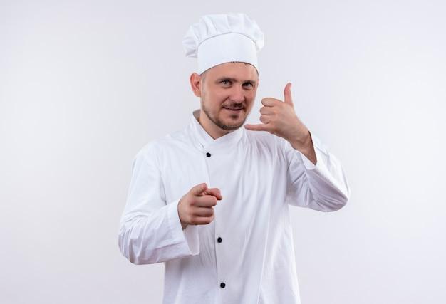 Erfreulicher junger hübscher koch in der kochuniform, die rufzeichen tut und lokal auf leerraum zeigt