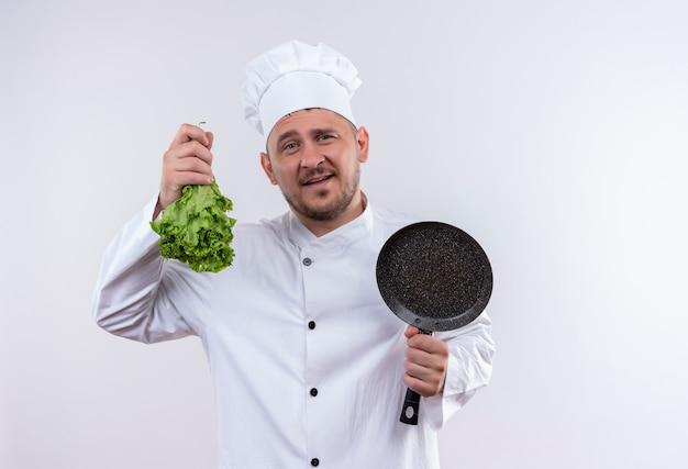 Erfreulicher junger hübscher koch in der kochuniform, die salat und bratpfanne auf isoliertem weißraum hält