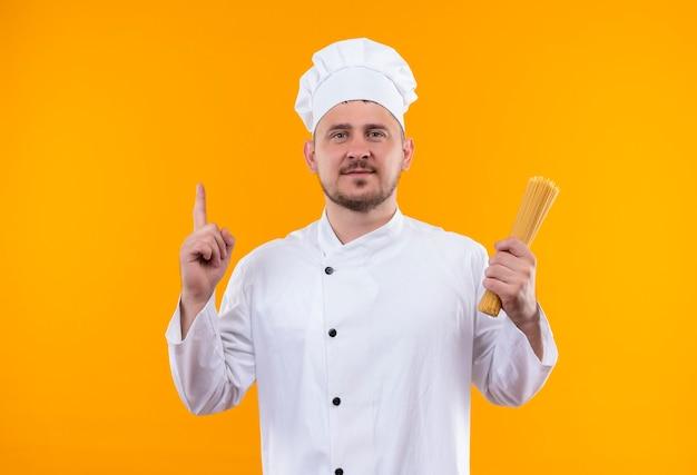 Erfreulicher junger hübscher koch in der kochuniform, die spaghetti-nudeln hält und lokal auf orange raum zeigt