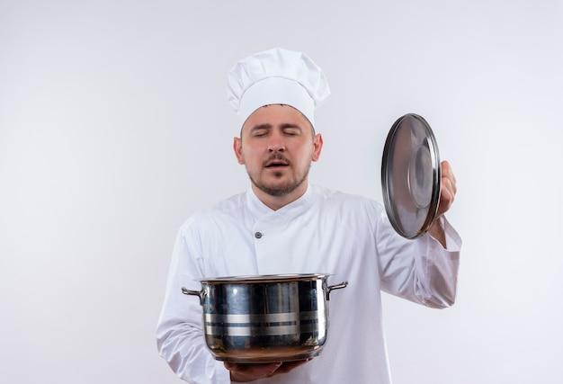 Erfreulicher junger hübscher koch in der kochuniform, die topf und topfdeckel mit geschlossenen augen lokalisiert auf weißem raum hält