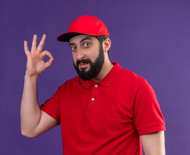 Erfreulicher junger hübscher lieferbote, der rote uniform und kappe tut, die ok zeichen lokalisiert auf lila wand tragen
