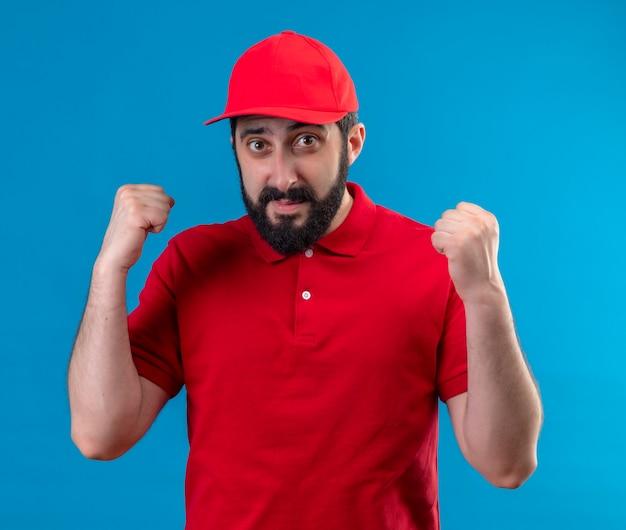 Erfreulicher junger hübscher lieferbote, der rote uniform und mütze trägt, die fäuste an der blauen wand isoliert hebt