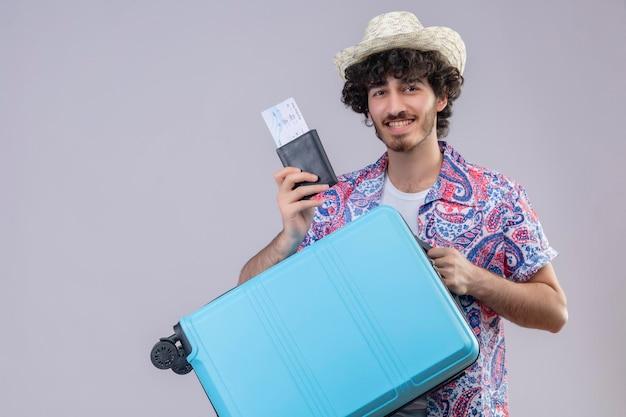 Erfreulicher junger hübscher lockiger reisender mann, der lächelnden hut trägt und brieftasche und flugtickets und koffer auf isoliertem weißem raum mit kopienraum hält