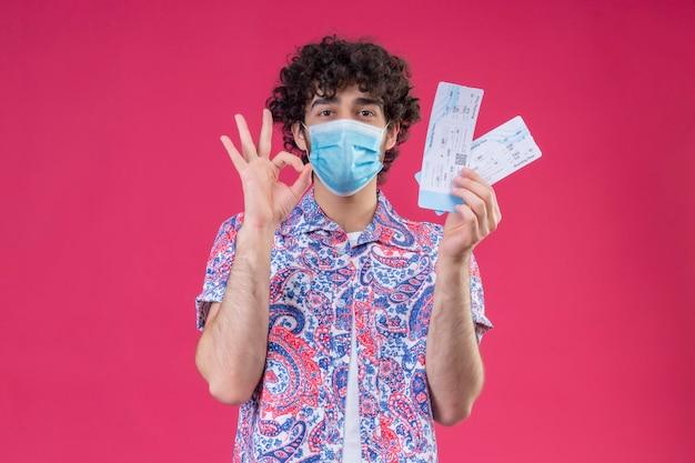 Erfreulicher junger hübscher lockiger reisender mann, der medizinische maske hält, die flugtickets tut, die ok zeichen auf lokalisiertem rosa raum mit kopienraum tun
