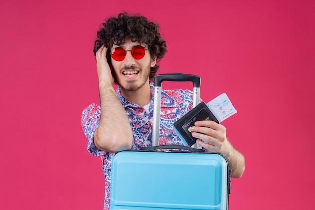Erfreulicher junger hübscher lockiger reisender mann, der sonnenbrillen hält, die flugtickets halten, brieftasche, die hände auf kopf und auf koffer mit geschlossenen augen auf isoliertem rosa raum mit kopienraum setzt