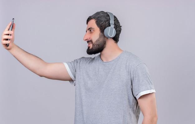 Erfreulicher junger hübscher mann, der kopfhörer hält und handy lokalisiert auf weißer wand hält
